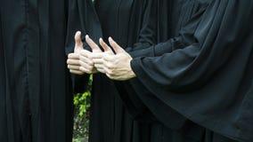 La gente con gli abiti neri di graduazione si batte su Fotografia Stock Libera da Diritti