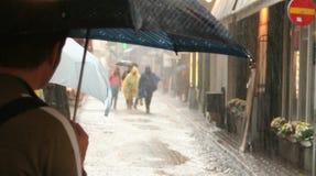 La gente con gli ombrelli nella pioggia fotografie stock