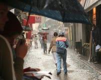 La gente con gli ombrelli nella pioggia Fotografia Stock Libera da Diritti