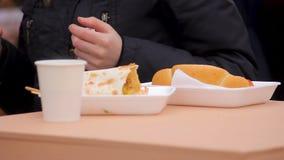 La gente con grande appetito che gode dell'alimento della via del ciarpame al festival dell'aria aperta archivi video