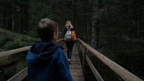 La gente con i bambini attraversa lentamente il vecchio ponte di legno stock footage