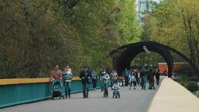 La gente con i bambini che camminano sul ponte nell'area del parco di ricreazione della città video d archivio