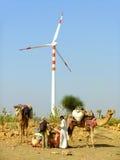 La gente con i cammelli che stanno generatore eolico vicino in deserto del Thar immagine stock
