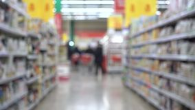La gente con i carrelli La gente sta comperando in un supermercato, fondo vago defocused stock footage