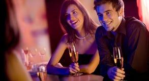 La gente con i vetri del champagne in ristorante, incontrantesi Fotografia Stock