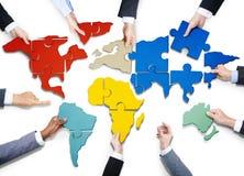 La gente con il puzzle che si forma nella mappa di mondo Immagini Stock Libere da Diritti