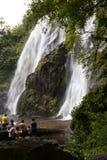 La gente con l'alta cascata Fotografia Stock