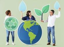 La gente con l'ambiente e le icone di riciclaggio Fotografia Stock