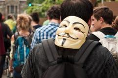 La gente con la maschera anonima durante la dimostrazione contro Monsanto e il transatlantique t Immagini Stock