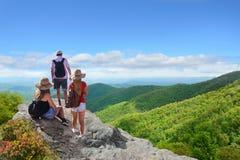 La gente con las mochilas que caminan el verano dispara en montañas Fotografía de archivo