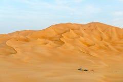La gente con las tiendas y los coches entre las dunas en al-Khali de la frotación abandona (O Fotos de archivo libres de regalías
