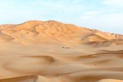 La gente con las tiendas y los coches entre las dunas en al-Khali de la frotación abandona (O Imagen de archivo