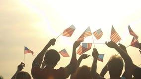 La gente con le bandiere americane al fondo del cielo di mattina stock footage