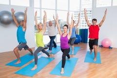 La gente con le mani sollevate facendo yoga Immagini Stock Libere da Diritti