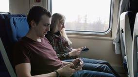 La gente con lo Smart Phone che viaggia in treno sopra permuta Passeggeri che utilizzano smartphone che permuta nel trasporto pub video d archivio