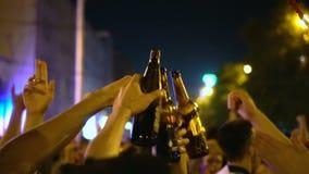 La gente con su entrega su botella principal del golpe de cóctel para la alegría