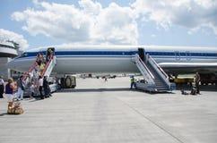 La gente consigue del avión en el aeropuerto imagenes de archivo