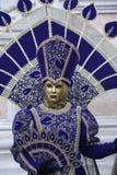 La gente in costume veneziano di carnevale in un costume variopinto e di porpora di carnevale ed in una maschera marroni, dell'or Fotografia Stock