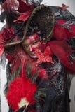 La gente in costume veneziano di carnevale in un costume variopinto di carnevale ed in una maschera rossi e neri Venezia Fotografia Stock Libera da Diritti