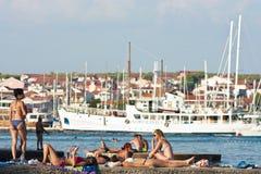 La gente in costumi da bagno che prende il sole sul pilastro sulla spiaggia immagine stock libera da diritti