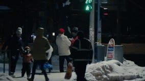 La gente cruza la calle de la noche a través del paso de peatones a una señal de tráfico verde Cuenta descendiente en el indicado almacen de video