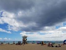 La gente cuelga hacia fuera en la playa con agua ondulada en el océano de Kaimana esté imagen de archivo libre de regalías