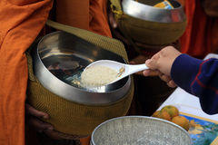 La gente da ofrendas pulidas del arroz a un monje budista Imagen de archivo libre de regalías