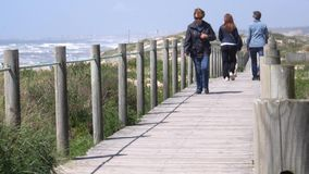 La gente da un paseo en el paseo mar?timo de madera cerca de la playa de Espinho, Portugal almacen de video