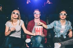 La gente de Interestd está mirando película en cine Son que se sientan y de miradas derecho a través de los vidrios especiales In Imágenes de archivo libres de regalías
