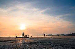 La gente de la silueta se relaja en la playa Imagen de archivo
