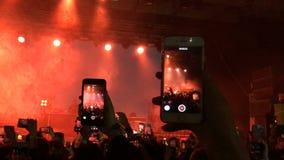 La gente de la muchedumbre sostiene el teléfono elegante en manos y tira el vídeo Teléfono celular de la toma del hombre metrajes