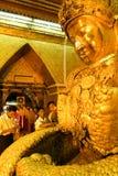 La gente de Myanmar veneró la estatua de Buda con el papel de oro Foto de archivo libre de regalías