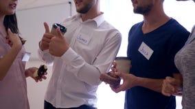 La gente de la oficina con las insignias sostiene el café con los bollos y la charla junta en el primer del tiempo de la rotura almacen de metraje de vídeo