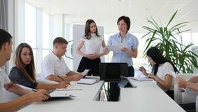 La gente de la oficina en el trabajo que discute negocio y al director se sostiene en informe del trabajo de manos en la sala de  almacen de video