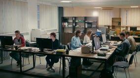 La gente de la oficina está trabajando junta en sus ordenadores en un escritorio metrajes