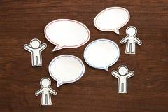 La gente de papel con discurso en blanco colorido del diálogo burbujea en la madera marrón Concepto de la comunicación foto de archivo