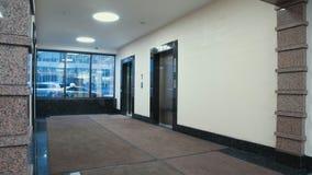 La gente de Timelapse camina a lo largo de vestíbulo con los elevadores en el centro almacen de video