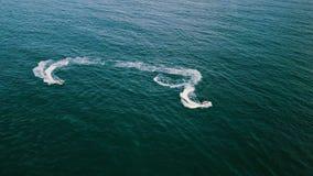 La gente de la visión aérea que monta en el jet esquía en la agua de mar Turistas que conducen en el esquí del jet metrajes