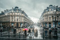 La gente debajo de los paraguas coloreados corre en la lluvia en las calles de París, Francia Foto de archivo libre de regalías