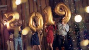 La gente del baile cerca de un árbol de navidad sostiene los globos de oro que hacen un número 2019 Concepto del Año Nuevo 2019 almacen de metraje de vídeo
