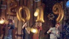 La gente del baile cerca de un árbol de navidad sostiene los globos de oro que hacen un número 2019 Concepto del Año Nuevo 2019 almacen de video