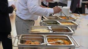 La gente del buffet ha messo l'alimento in piatti video d archivio
