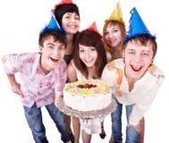 La gente del grupo en sombrero del partido come la torta. Imagen de archivo libre de regalías