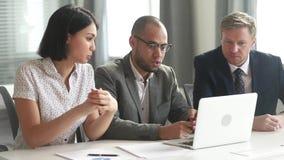La gente del gruppo di affari confronta le idee avendo discussione che esamina il computer portatile archivi video