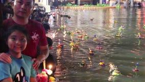 La gente del lapso de tiempo trae boyante adornada al río en el festival de Loykratong en el día de la Luna Llena del duodécimo m almacen de video