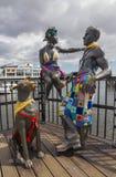 La gente del Ni de Pobl Fel le gusta nosotros estatua en el paseo marítimo de la bahía de Cardiff, País de Gales Imagen de archivo