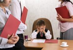 La gente dell'ufficio che si leva in piedi intorno al loro capo del bambino Fotografie Stock Libere da Diritti