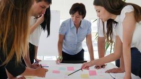 La gente dell'ufficio si avvicina allo scrittorio che discute lo sviluppo di affari di idee al lavoro archivi video