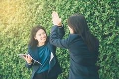 La gente della donna di affari due alta fiving all'aperto il fondo della natura Immagine Stock