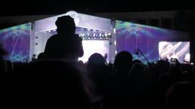 La gente della folla al concerto di musica Folla incoraggiante davanti alle luci variopinte luminose della fase siluette della fo stock footage